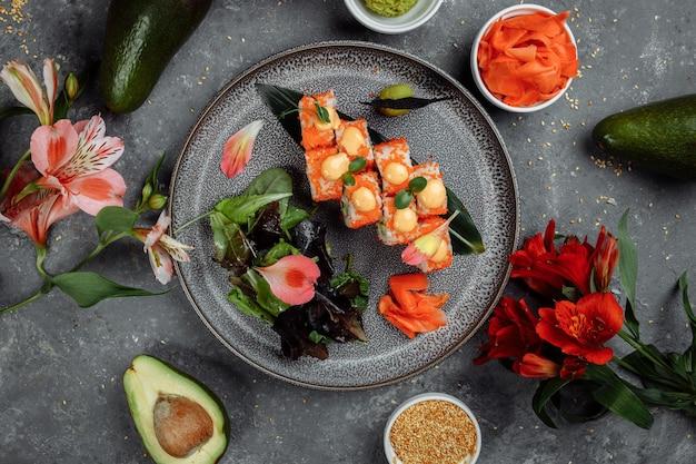 Sushi roll z łososiem, tuńczykiem, awokado, serkiem z krewetkami królewskimi, kawior philadelphia, tobica chuka. menu sushi. japońskie jedzenie.