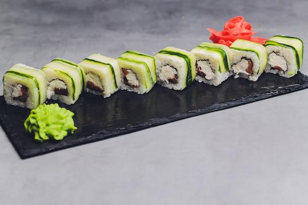 Sushi roll z ogórkiem, sezamem i serem philadelphia. japońskie jedzenie. tradycyjne sushi. widok z góry.