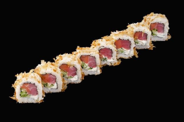 Sushi roll z tuńczykiem, łososiem wędzonym na zimno, serem feta, ogórkiem, płatkami tuńczyka na czarnym tle