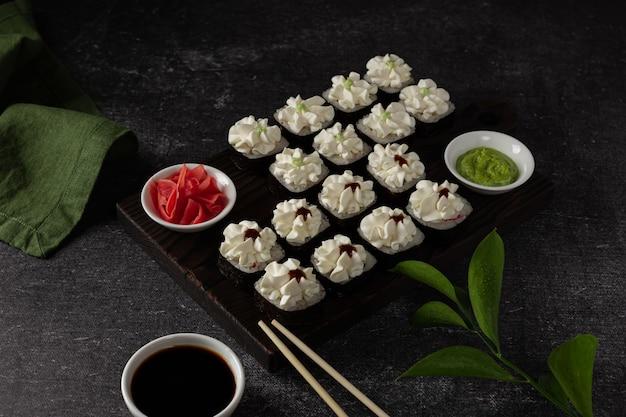 Sushi roll z wędzonym łososiem z serkiem awokado na czarnym tle menu sushi japońskie jedzenie