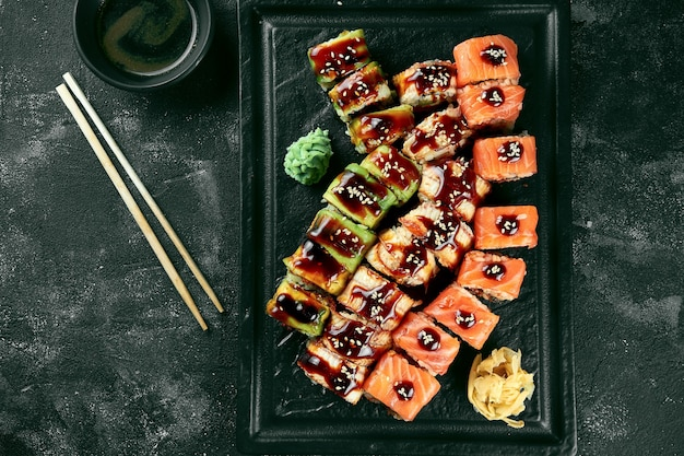 Sushi roll zestaw trzech smoków z węgorzem i łososiem na czarnej płycie na ciemnym tle. dostawa jedzenia. kuchnia japońska