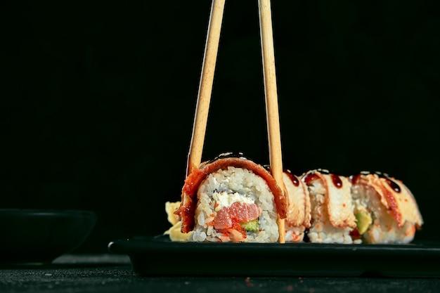 Sushi roll złoty smok z węgorzem i łososiem na czarnej płycie na ciemnym tle. dostawa jedzenia. kuchnia japońska