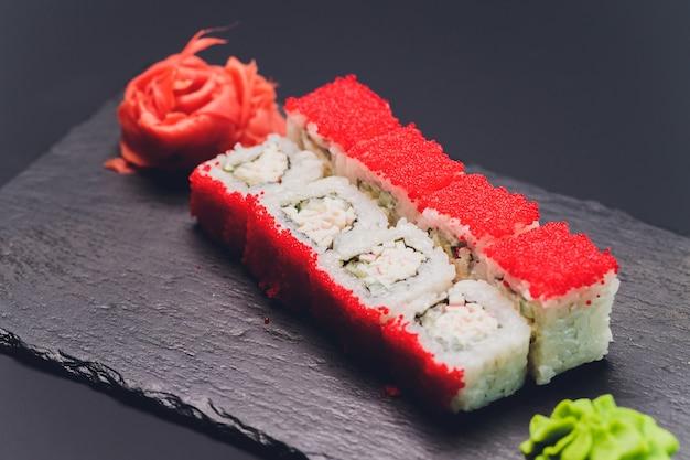 Sushi rolls - czerwony smok z kawiorem tobiko i łososiem. tradycyjna kuchnia japońska. widok z góry.