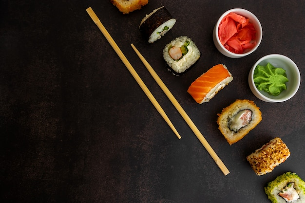 Sushi różnych typów na ciemnym tle widok z góry, z miejscem na tekst sushi różnych typów na ciemnym tle widok z góry, z miejscem na tekst