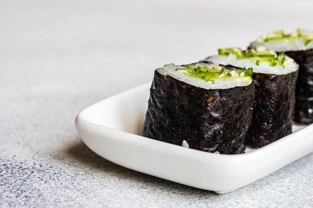 Sushi set sashimi i sushi rollsy podawane na kamiennym łupku