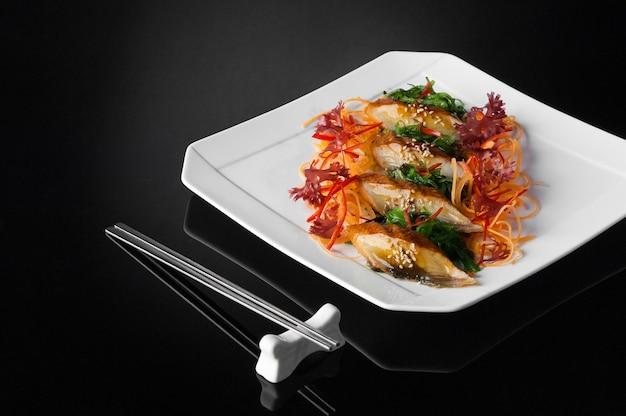 Sushi w białym talerzu z pałeczkami na czarnym tle z odbiciem