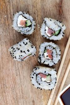 Sushi z białego ryżu, pstrąga i awokado, gotowe do spożycia produkty warzywne i łosoś z czerwonej ryby