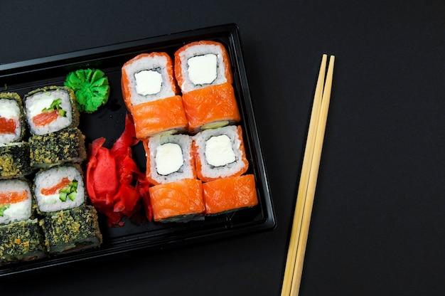 Sushi z sosem i drewnianymi patyczkami na czarnym tle
