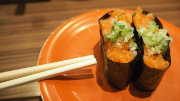 Sushi z surowego łososia zawijanego z wodorostami. to japońskie jedzenie.