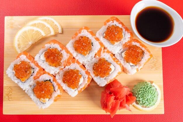Sushi, z twarogiem, łososiem i kawiorem. na desce. na czerwonym tle. w dowolnym celu.