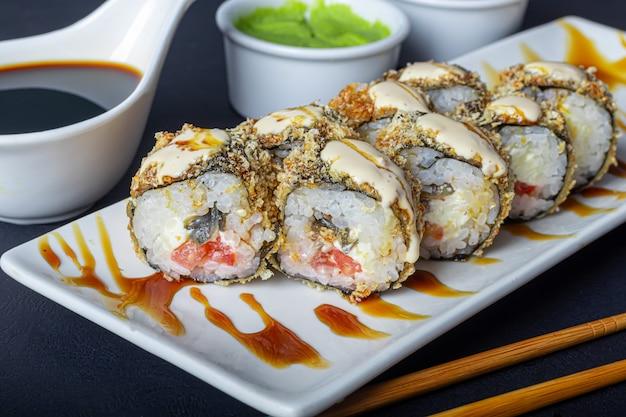 Sushi zestawy uramaki, kalifornia, filadelfia, na białym talerzu. w pobliżu imbir i wasabi.