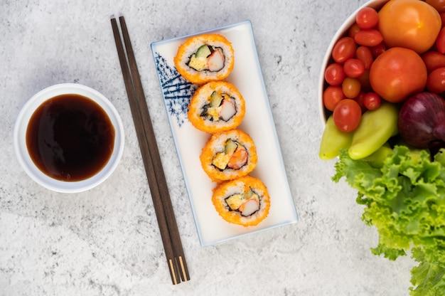 Sushi znajduje się na talerzu z pałeczkami i sosem do zanurzania na podłodze z białego cementu.