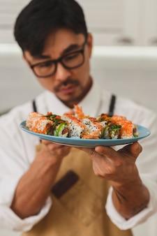 Sushi zrobienie w procesie z bliska na rękach szefa kuchni trzyma talerz z rolkami