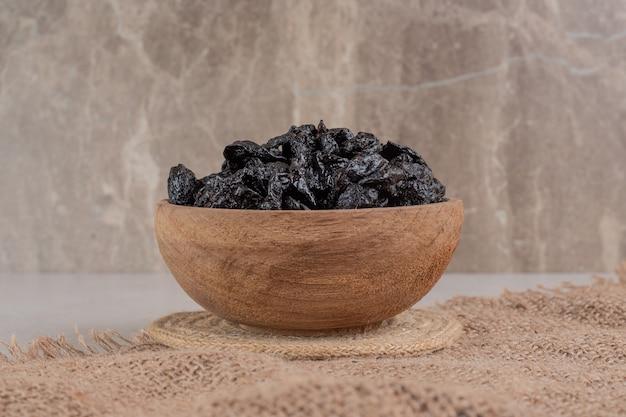 Susz czarne śliwki w drewnianym kubku na kawałku płótna.