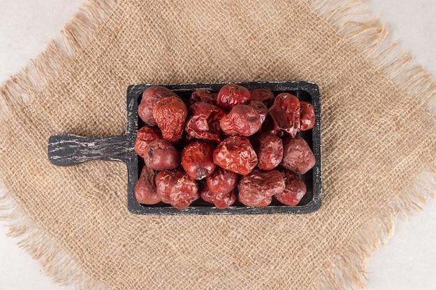 Susz jagody jujube na rustykalnym drewnianym talerzu.