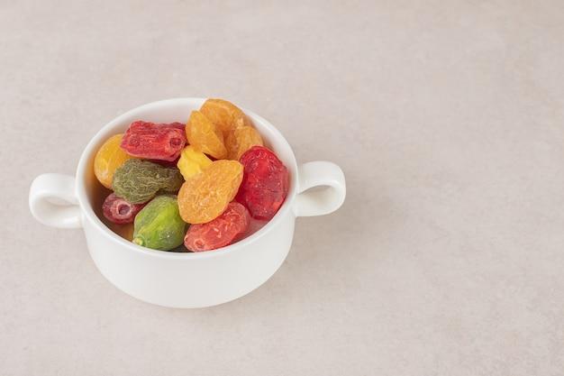 Susz kolorowe wiśnie w ceramicznym kubku.