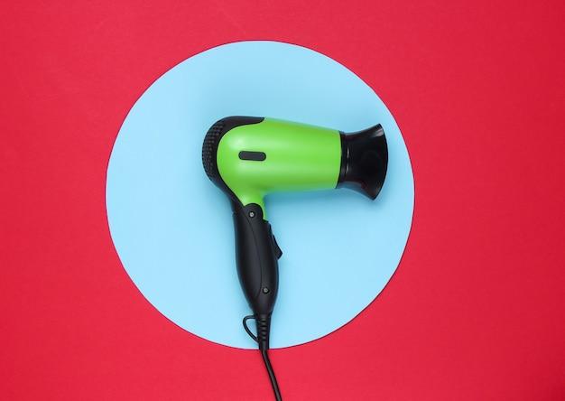 Suszarka do włosów na czerwonym tle z niebieskim pastelowym kółkiem. kreatywne minimalistyczne piękno i moda martwa natura. widok z góry