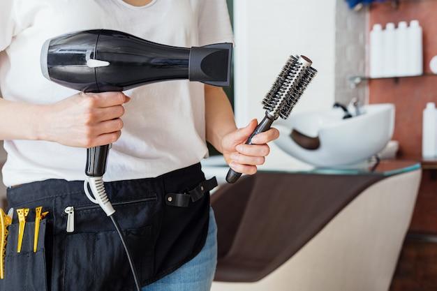 Suszarka do włosów, szczotka grzebieniowa w dłoniach fryzjerskich przeciwko salonowi kosmetycznemu, wnętrze sklepu fryzjerskiego, umywalka z umywalką. profesjonalne narzędzia fryzjerskie.