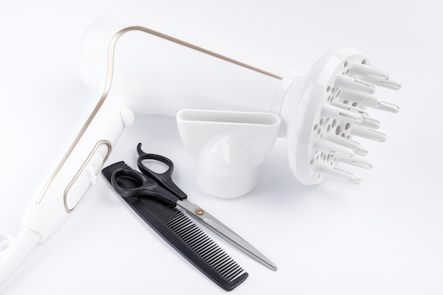 Suszarka do włosów z różnymi nasadkami, nożyczkami i grzebieniem na białym tle.