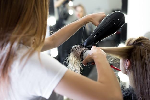 Suszenie długich blond włosów za pomocą suszarki do włosów i okrągłej szczotki