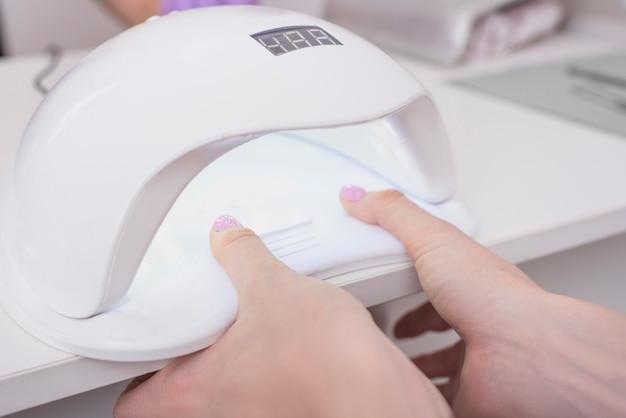 Suszenie paznokci w lampie ultrafioletowej. manicure salonowy. ścieśniać.