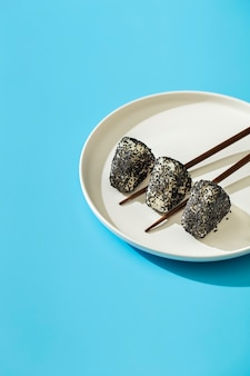 Suszi rolki z sezamowymi ziarnami na talerzu