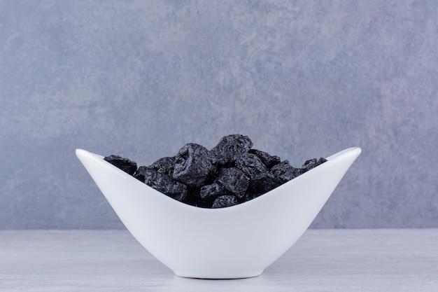 Suszona czarna sułtanka w misce na betonowym tle. zdjęcie wysokiej jakości