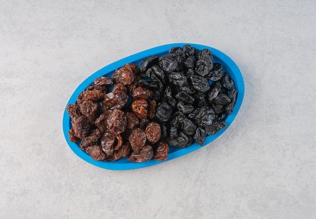 Suszona czarna wiśnia i śliwki na niebieskim półmisku.
