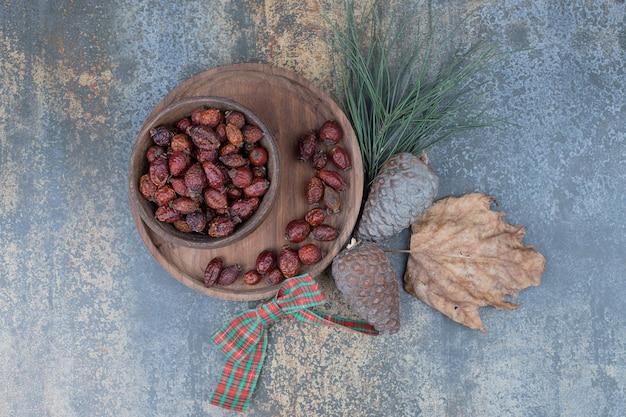 Suszona dzika róża i szyszki z kokardą na marmurowym stole