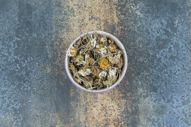 Suszona herbata rumiankowa w fioletowej misce.