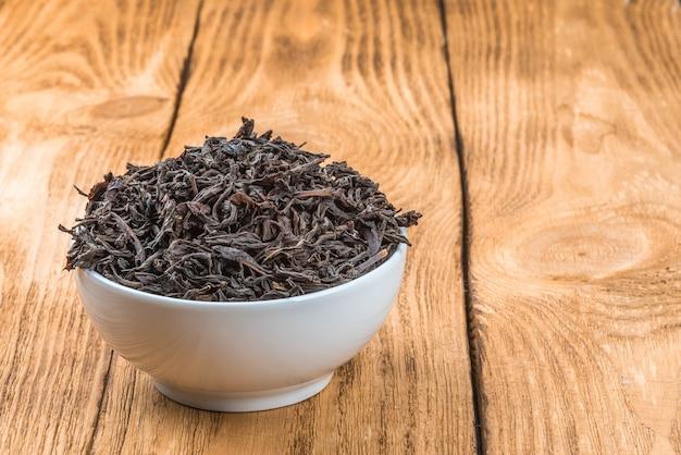 Suszoną herbatę nalewa się do ceramicznego kubka na drewnianym stole.
