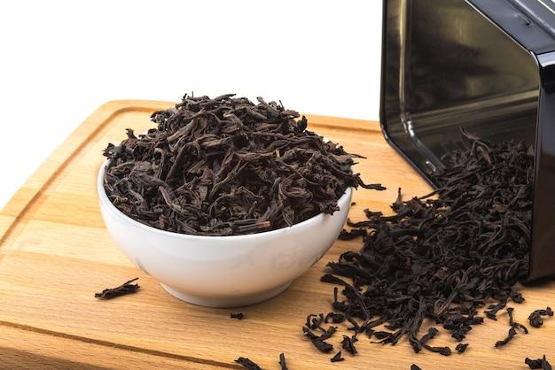 Suszoną herbatę przelewa się do ceramicznego kubka na drewnianej desce na białej powierzchni.