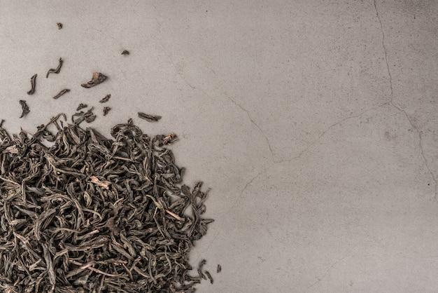 Suszoną herbatę rozlewa się na szarej teksturowanej powierzchni.