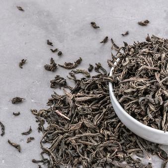 Suszoną herbatę wlewa się do białej ceramicznej filiżanki na szarym tle z teksturą.