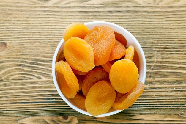 Suszona i odwodniona morela żółta, leżąca w szklanej misce i gotowa do użycia jako słodki, zbliżenie