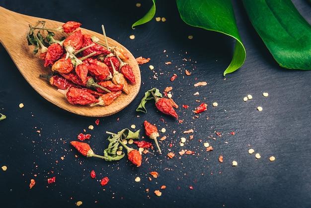 Suszona papryczka chili mini na czarnej powierzchni łupkowej z zielonym liściem monstery.