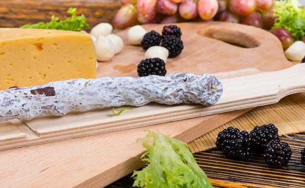 Suszona peklowana pikantna kiełbasa gotowa do pokrojenia i wystawienia na stole bufetowym z bukietem serów, jeżyn, cebuli koktajlowej i winogron