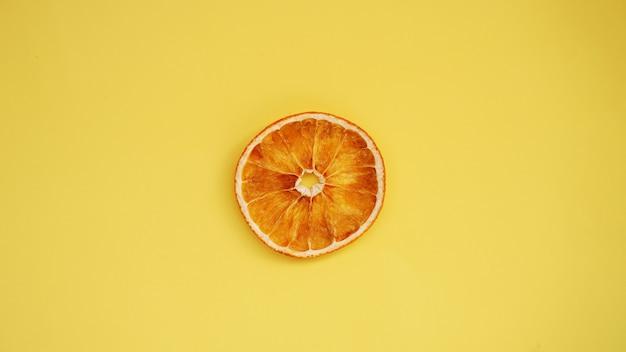 Suszona pomarańcza na żółtym tle. suszone makro plasterek pomarańczy