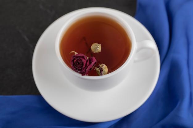 Suszona róża w filiżance gorącej herbaty na czarnym stole.