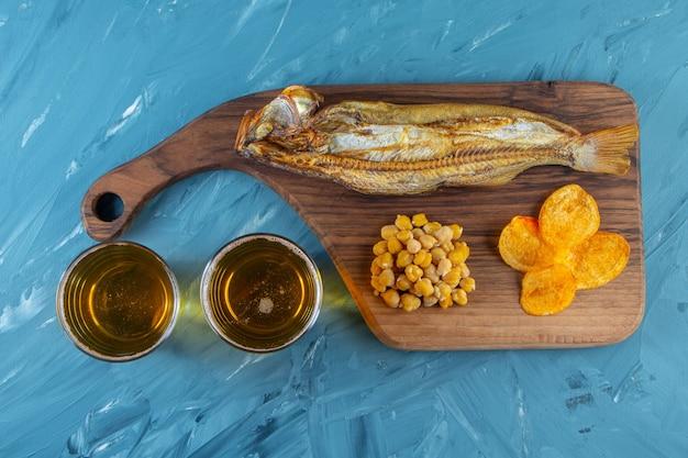 Suszona ryba, frytki, ciecierzyca na desce do krojenia obok szklanki piwa, na niebieskiej powierzchni.