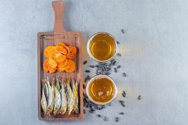 Suszona ryba i chipsy chlebowe na desce obok szklanki piwa, na marmurowym tle.