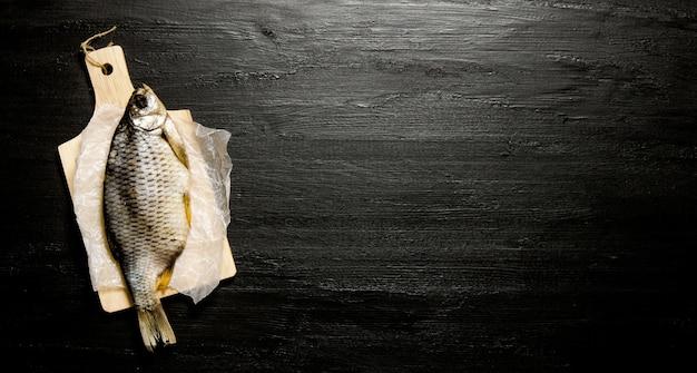 Suszona ryba na drewnianej desce. na czarnej tablicy