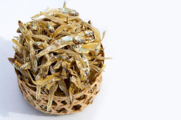 Suszona sardela w bambusowym koszu na białym tle