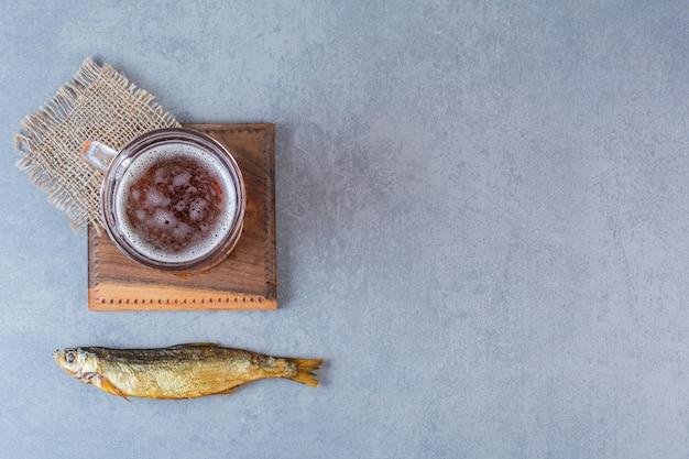 Suszona solona ryba i kufel piwa na desce na marmurowej powierzchni