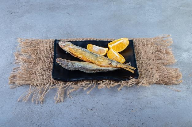 Suszona solona ryba i pokrojona cytryna na półmisku na jutowej serwetce, na marmurowej powierzchni.