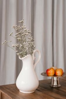 Suszone białe kwiaty w białym wazonie i jabłka na drewnianym stole