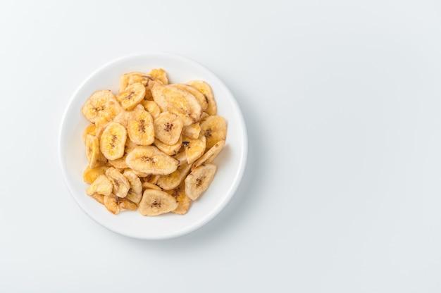 Suszone chipsy bananowe na białym tle