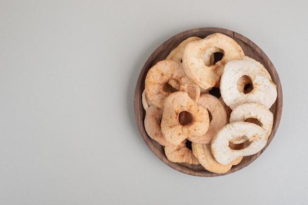 Suszone chipsy jabłkowe na drewnianym talerzu