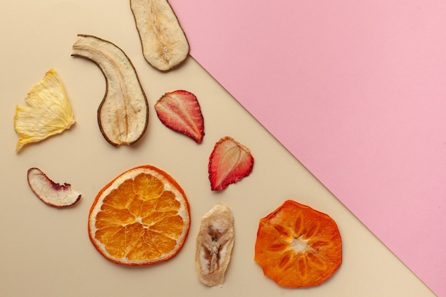 Suszone chipsy owocowe na różowej powierzchni
