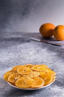 Suszone chipsy pomarańczowe w talerzu i świeże owoce pomarańczowe z nożem